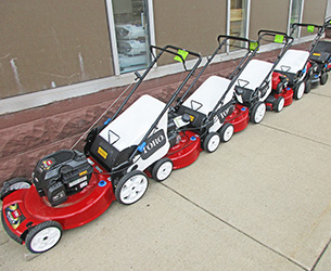 A row of red Toro walk-behind lawn mowers