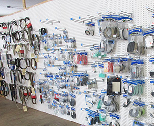 A wall with racks of power equipment parts and belts