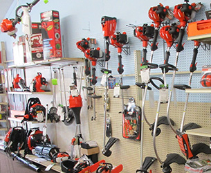 A wall with hanging power string trimmers